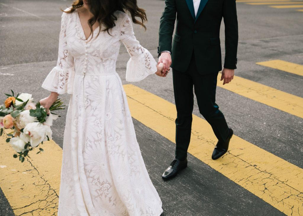 wedding couple crossing the street in yellow striped crosswalk