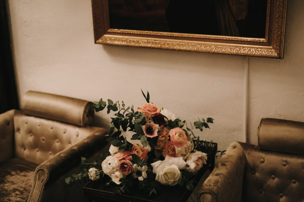 bridal bouquet on table in between two vintage chairs carondelet house